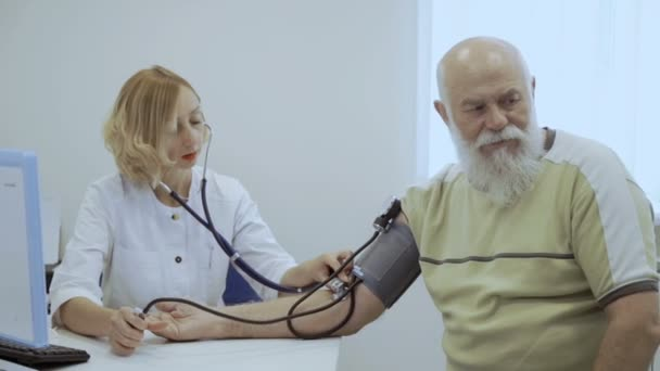 Doctor check the pulse of senior man with mechanic tonometer. Old man has a problem with heart and he visit cardiologist.