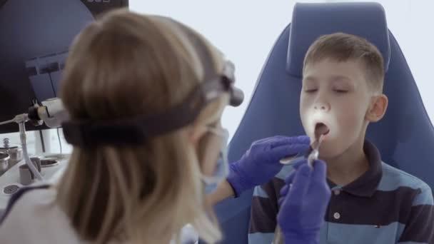 Lékař zkoumat pacienta krku Ent dalekohledem a nahlédni do úst dítěte. Malý chlapec zkontrolovat jeho krku v ORL v moderní klinika