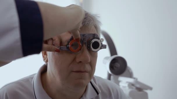 Doktor zkontrolovat mans pohled s optické zkušební snímek. Starší muž má špatný zrak a změnami očního lékaře v moderní klinika