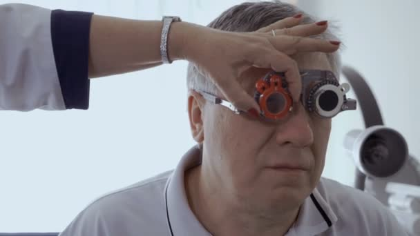 Doctor check mans sight with optical trial frame. Senior man has a bad eyesight and check it in ophthalmologist in modern clinic.
