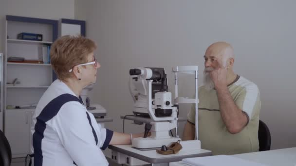 Doctor talks with patient after the procedure of checking eyesight. The man look on the doctor sitting near optical modern equipment.