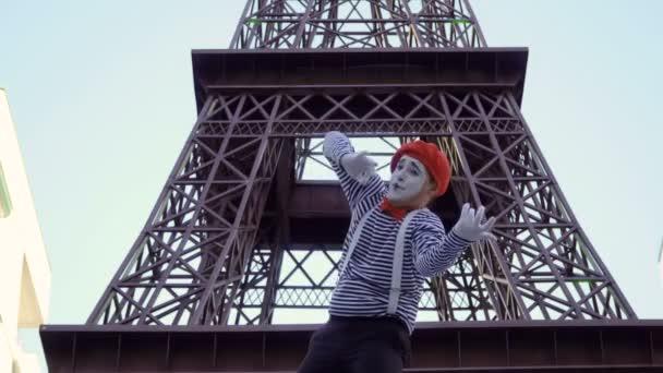 Mime mit gestreiftem Hemd und roter Baskenmütze posiert in der Nähe des Eiffelturms für die Kamera. Straßenschauspieler verdienen Geld in lustigen Rollen und spielen mit seiner Mimik.