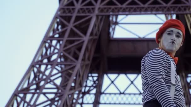 Muž na sobě mime svlékl košili a červený baret pózuje pro kameru v blízkosti Eiffelovy věže. Pouliční herec vydělat peníze zábavné role hrát a hrát si s jeho výrazy obličeje