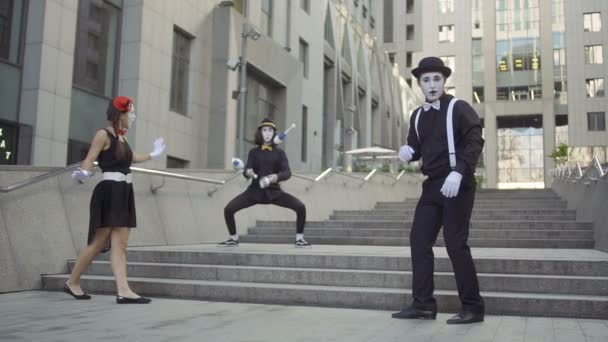 Mimes applauding to their colleague professionally juggling pins