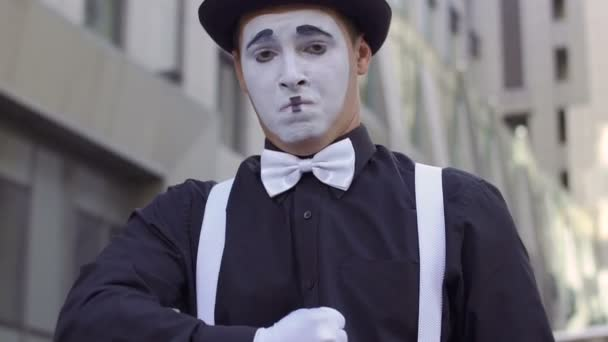 Funny mime in hat singing on camera
