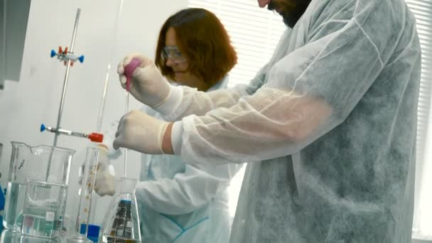 Two chemists working in the laboratory. The man is pouring acid into a flask. Woman observe after the assistant and working with fluids.