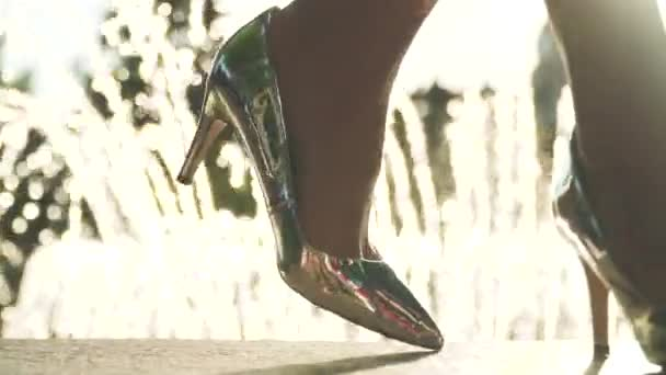 Frau in eleganten silbernen Schuhen auf Stöckelschuhen in der Nähe von Springbrunnen