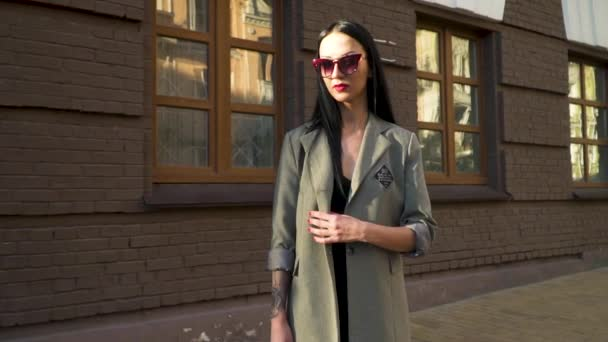Elegance brunette in coat and sunglasses moving in slow motion