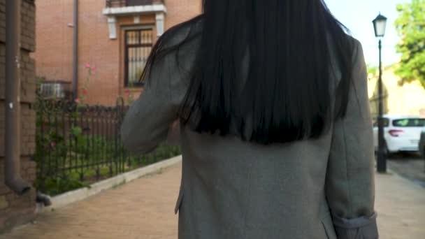 Dlouhé vlasy bruneta v šedém kabátě na městské ulici