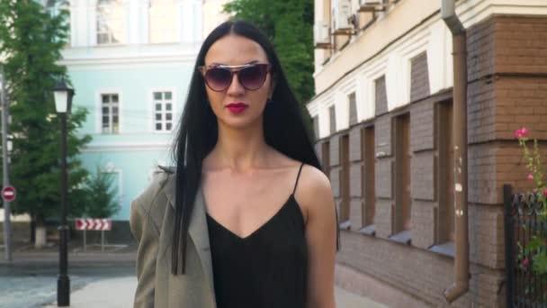 Stylově a důvěryhodně žena v sluneční brýle na městské ulici, pomalý pohyb
