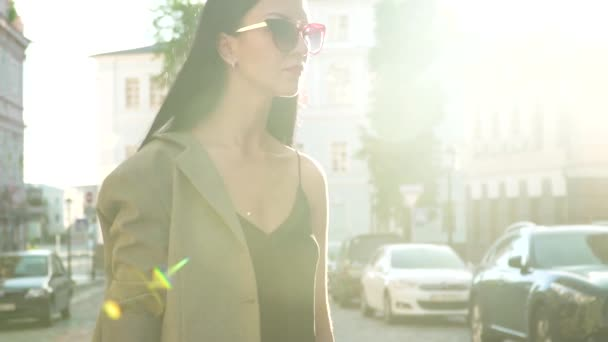 Young stylish brunette in sunglasses in sun rays in slow motion
