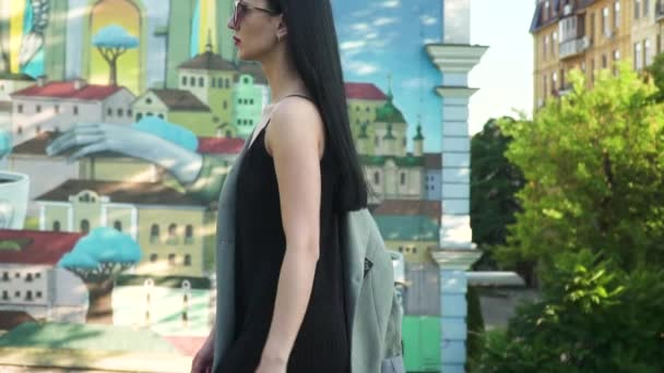Stylish woman in black dress and sunglasses walk in slow motion against graffiti