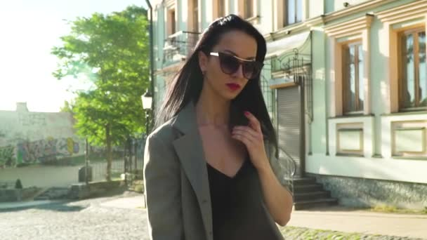 Stylish woman in sunglasses walking at the street in slow motion