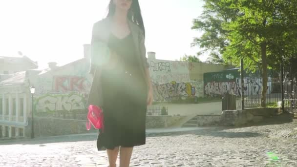 Fashionable woman with stylish pink bag walk in slow motion in sun rays