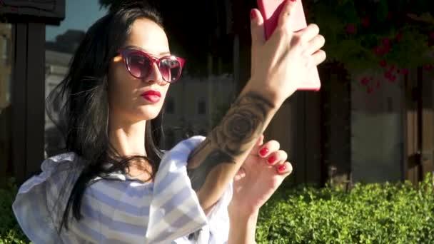 Elegantní brunetka v sluneční brýle s tetováním na ruce udělat selfie na její telefon