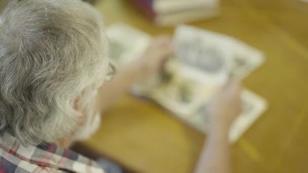 Starší muž hledá černé a bílé fotografie svého mládí