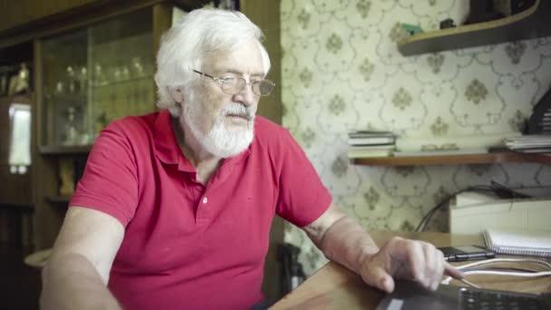 senior muž pomocí notebooku doma