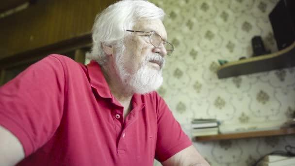 Mature man watching film at laptop at home