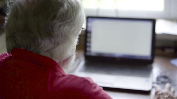 Ältere Mann mit Laptop am Tisch zu Hause
