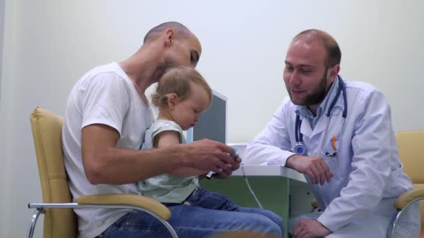 Junger Vater mit kleinen Tochter bei der Kinderarzt Beratung