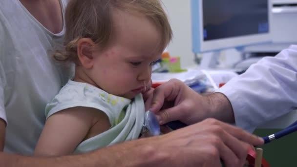Kinderarzt hört die Atmung von kleinen Mädchen mit Stethoskop