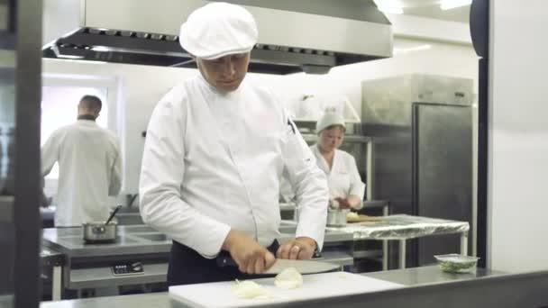 Kuchař dělené cibule v kuchyni restaurace