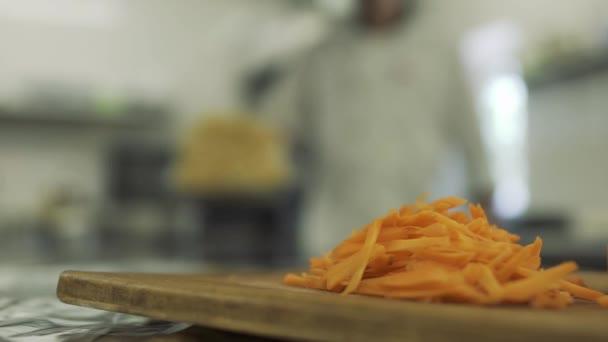 Cuuted mrkev na prkénku, šéfkuchař v rozmazané pozadí
