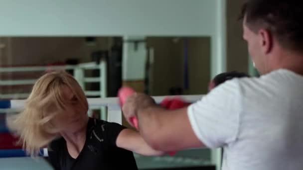 Junge Frau trainiert mit Trainer im Boxring
