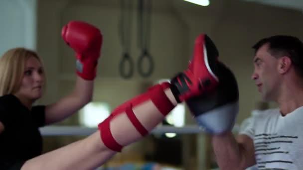 Sportovní žena školení hity kickbox s její nohou s trenérem