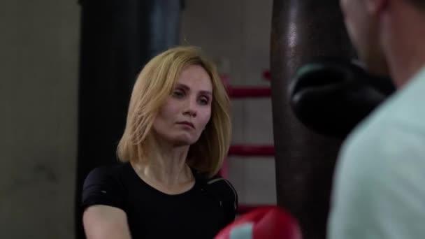 Schöne Frau mit Sportbekleidung und Boxhandschuhe training mit Trainer im Boxring. Hübsche Frau Training Kickboxen schlägt mit Bein und konzentriert am Hits. Konzept der Weiblichkeit in Mens sport.