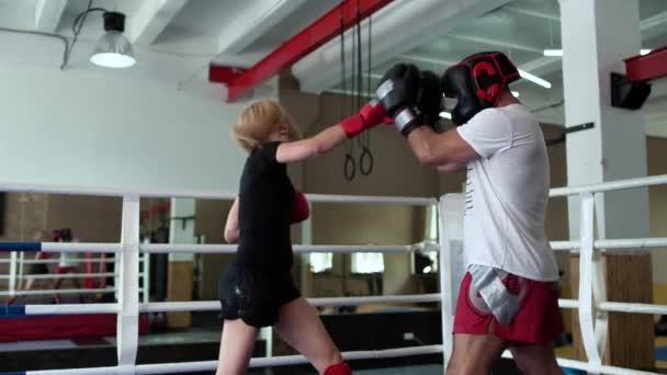 Hübsche Frau in Sportbekleidung arbeitet an Blastechnik mit Trainer im Boxring