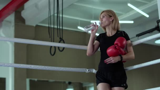 Woman stand at boxing ring and drink water