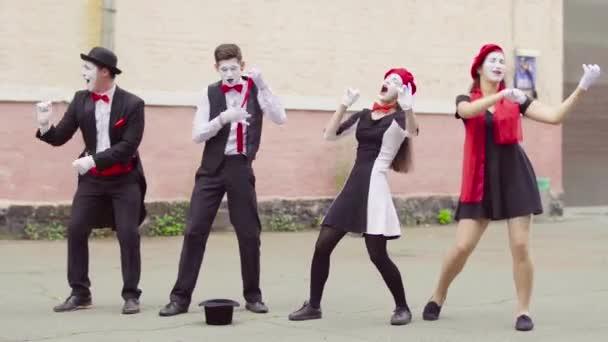 Vier Mimen spielen auf unsichtbarem Musikinstrument