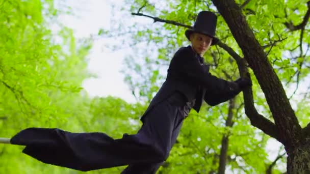 Junger Mann im Kostüm läuft auf Stelzen im Park neben Baum