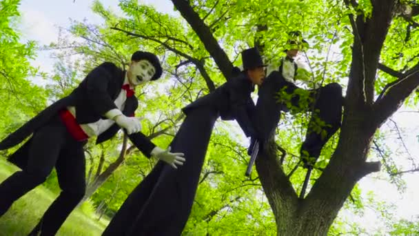 Pantomime und Straßenkünstler auf Stelzen spielen im Park