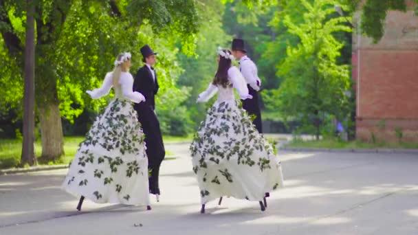 Dva páry krásy na chůdách tančí na ulici