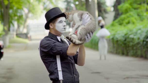 Komiker scherzt mit Katze auf der Straße