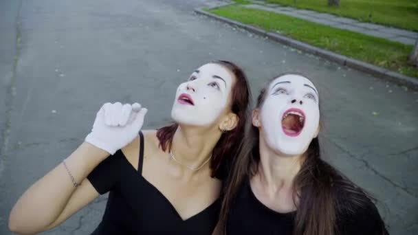 Two girls mimes imitate embarrassment when see camera