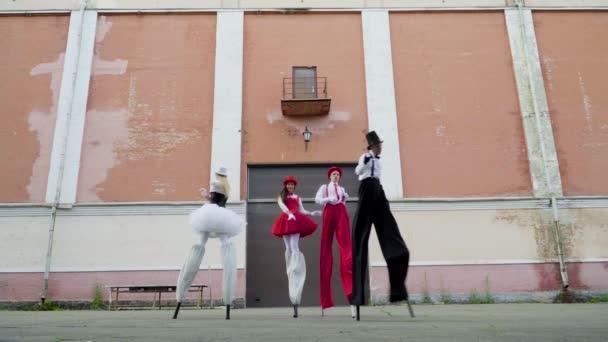 Dva páry na chůdách tančí poblíž budovy