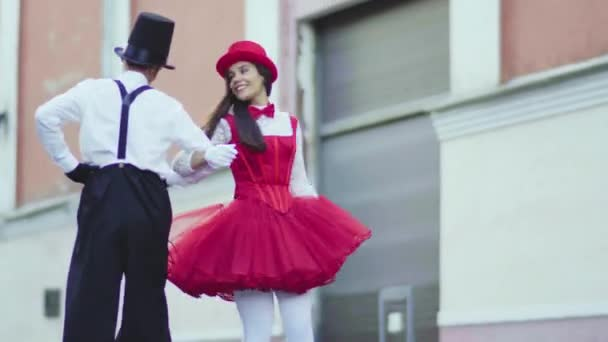 Funny comic couple on stilts dancind cool