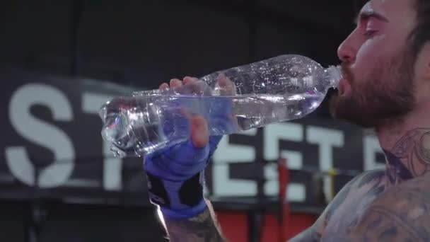 Handsome man with a tattoo is drinking water from a bottle