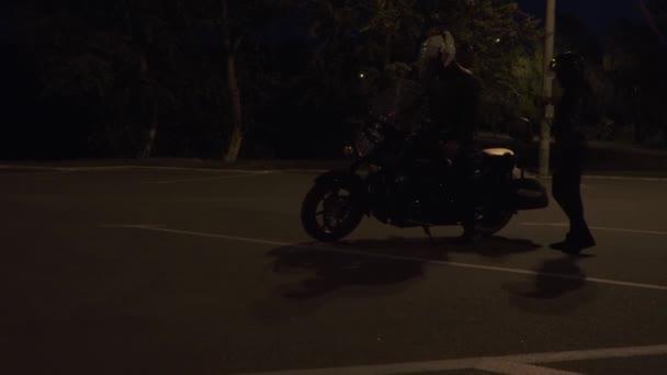 Dva motorkáři sedět na své motorce a rozjezd v noci na silnici