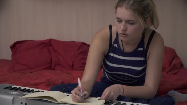 Beautiful girl with blond hair writes in a notebook