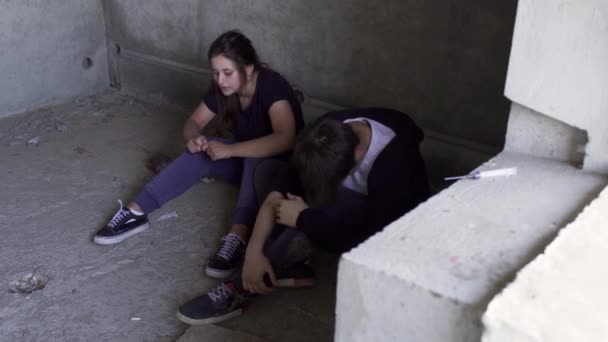 Two people sitting at the floor at the background of used syringe