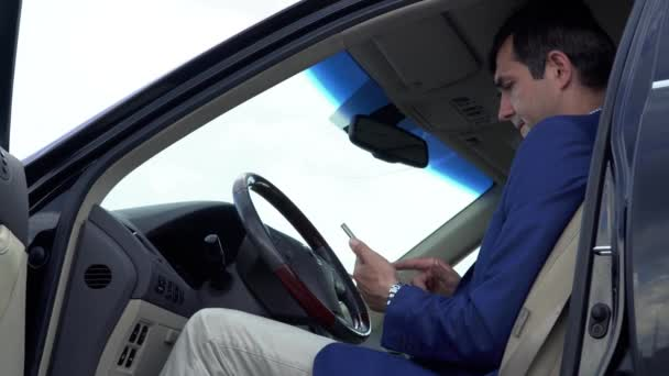 Successful businessman is having a business conversation in the car by phone