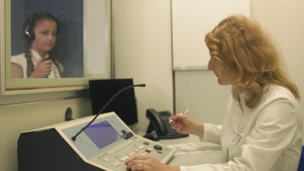 Lékař kontroluje slyšení s vybavením