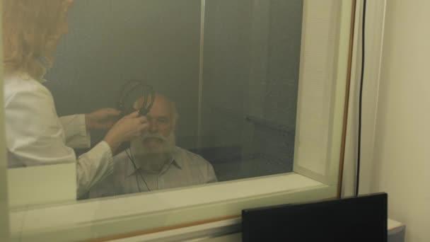 Doktor dá sluchátka na dospělého muže