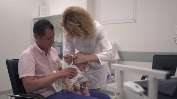 Liebender Vater hält seine kleine Tochter im Krankenhaus in den Armen