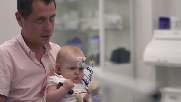 Dad is holding a baby with medical sensors on hands