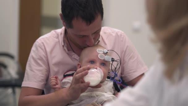 Papa hält Baby mit medizinischen Sensoren auf Händen